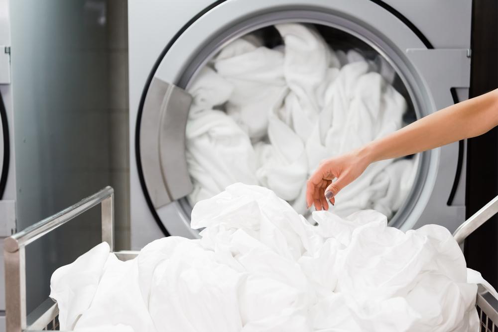 Woman washing load of new sheets - should you wash new sheets